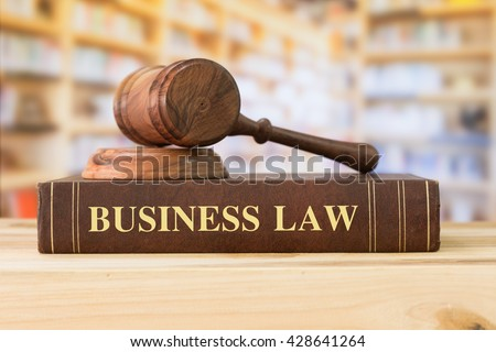 Business Law books with a judges gavel on desk in the library. Legal education concept.