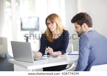 Portrait of investment advisor businesswoman sitting at office in front of computer and consulting with young professional man.  Royalty-Free Stock Photo #428774194