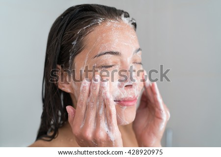 Skincare woman washing face in shower foaming facewash soap scrub on skin. Asian female adult cleaning body showering in hot water at home on in hotel as morning routine. Enjoying relaxing time. #428920975