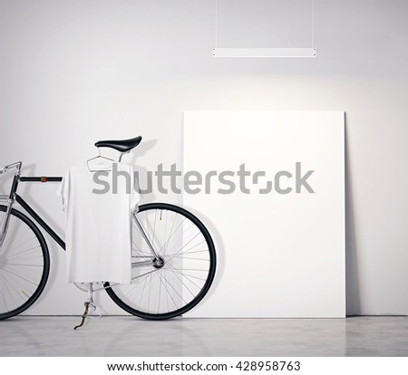 Photo Interior Modern Studio Loft with Concrete Wall and Classic bicycle.Empty White Canvas on Floor, Spotlight top. Blank Tshirt hanging Bike. Square mockup