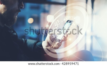 Picture businessman relaxing modern loft office.Man sitting in chair at night.Using contemporary smartphone,blurred background. Digital Connections World Wide Interfaces.Horizontal,film effect