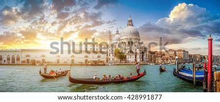 Beautiful view of traditional Gondolas on famous Canal Grande with historic Basilica di Santa Maria della Salute in the background in romantic golden evening light at sunset in Venice, Italy #428991877