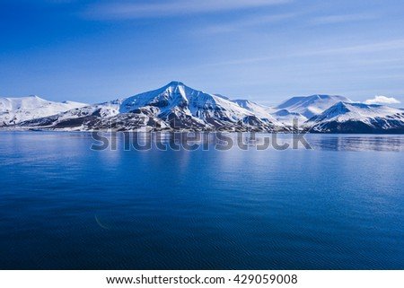 landscape of the Arctic Ocean and reflection with blue sky and mountains with snow on a sunny day, Norway, Spitsbergen, Longyearbyen, Svalbard, summer, winter Royalty-Free Stock Photo #429059008