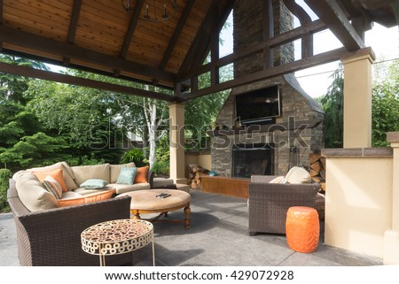 An upscale backyard terrace featuring perennials and with a custom designed shelter and fireplace. #429072928