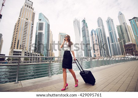 Businesswoman pulling a suitcase in a big city. #429095761