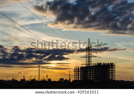 Industrial construction cranes and building silhouettes over sun at sunrise #429161011