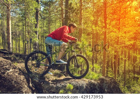 Man with the bike standing on a rock. summer nature #429173953