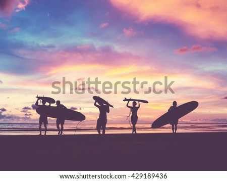Silhouette Of surfer people carrying their surfboard on sunset beach, vintage filter effect with soft style Royalty-Free Stock Photo #429189436