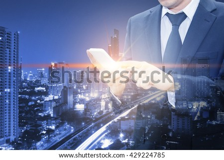 Double exposure of businessman touching with smart phone world business network connection and city center of business, communication business and finance concept #429224785