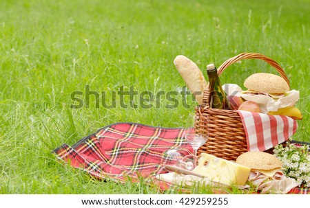 Picnic basket with apples bread cheese wine and sandwiches #429259255