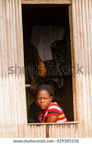 PORTO-NOVO, BENIN - MAR 9, 2012: Unidentified Beninese girl looks out of the window. People of Benin suffer of poverty due to the difficult economic situation #429385558