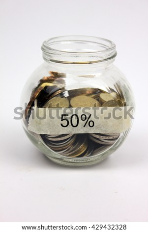 Coins in a glass container with a label 50%. Financial concept. #429432328