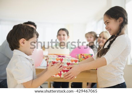 Caucasian girl giving brother birthday gift at party