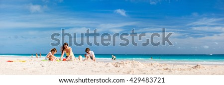 Mother and kids making sand castle at tropical beach #429483721