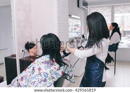 Dneprodzerzhinsk, Ukraine - March 28, 2016: Hairdresser makes hairstyle to the client of beauty salon #429565819