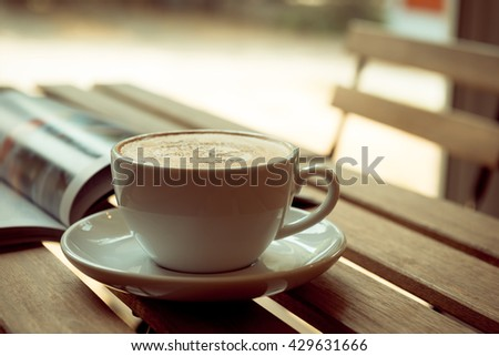 mug of hot coffee and opened book on table near windows #429631666