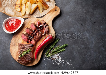 Grilled sliced beef steak on cutting board over stone table. Top view with copy space #429647527