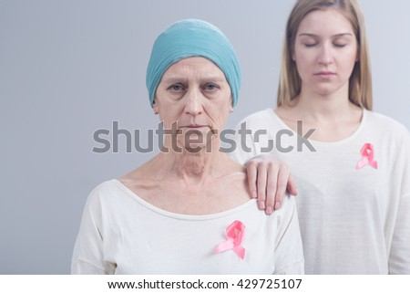 Picture of mother and daughter wearing pink ribbons, an international symbol of breast cancer awareness
