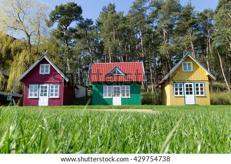 three multi-colored small tiny house on the lawn in the forest Royalty-Free Stock Photo #429754738