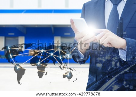 Double exposure of businessman using smart phone network connection world map by NASA and city of business , blurred cargo distribution warehouse, international transportation trading business concept #429778678