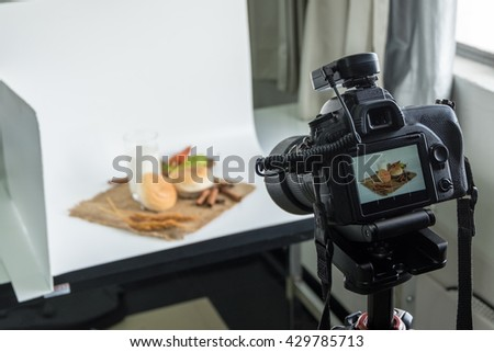 DSLR camera to shooting bread and glass of milk in  indoor photo studio