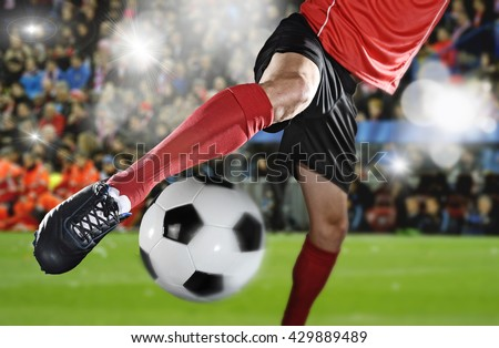 close up legs and soccer shoe of football player in action kicking ball wearing red jersey and sock playing on stadium with audience flashes  and lens flare on the background
