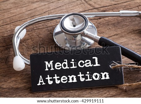 Stethoscope on wood with Medical Attention words as medical concept #429919111