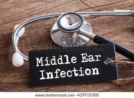 Stethoscope on wood with Middle Ear Infection words as medical concept #429919300