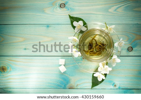 Cup with green highland leaf tea with jasmine, lump sugar on wooden turquoise table. Soft focus, vignette. #430159660