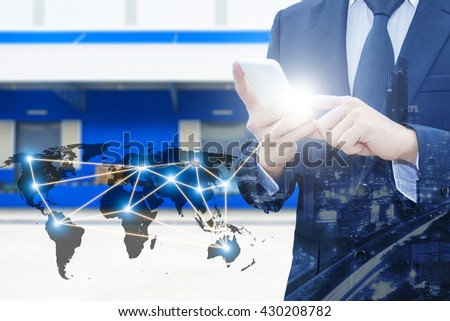 Double exposure of businessman using smart phone network connection world map by NASA and city of business , blurred cargo distribution warehouse, international transportation trading business concept #430208782