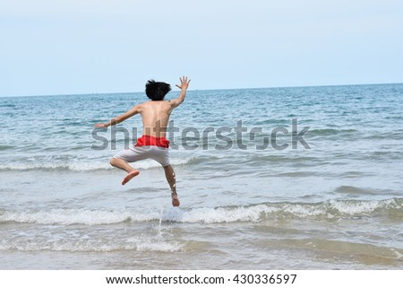 A man jumps in ocean waves. Jump with splashing water Summer Sunny Day #430336597