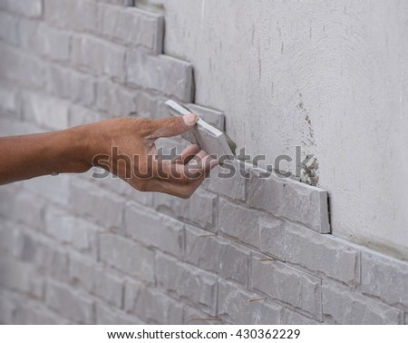 worker install stone wall tile with cement for house decoration #430362229