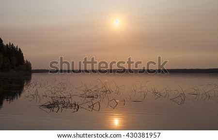 Sun after it has just risen over a lake in Saskatchewan Canada #430381957