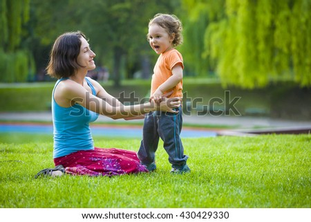 Young mother playing with baby on the grass in the Park. #430429330