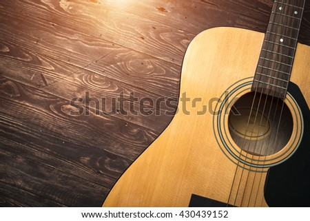 Acoustic guitar resting against a wooden background with copy space #430439152