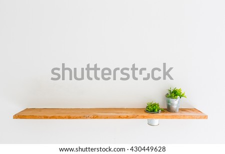 Wooden shelf on white wall with green plant. Royalty-Free Stock Photo #430449628