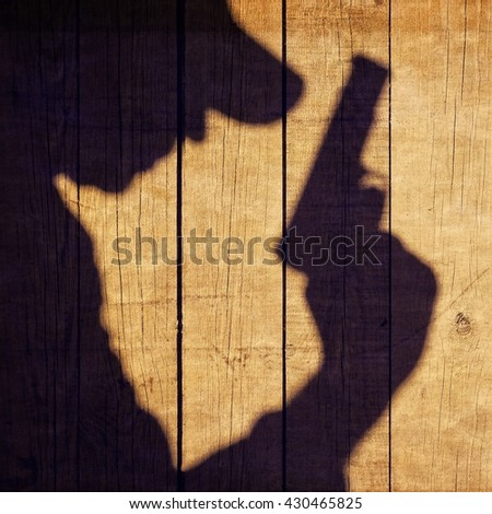 The Black Shadow Of A Man With A Handgun On The Wooden Wall. Black Armed Male Silhouette On The Wooden Fence. #430465825