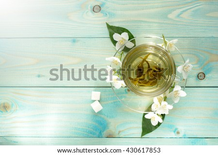 Cup with green highland leaf tea with jasmine, lump sugar on wooden turquoise table. Soft focus, lights effects. #430617853