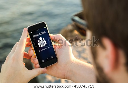 man on the coast using his smartphone setting privacy data. All screen graphics are made up. #430745713