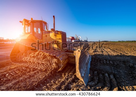 Beautiful sunset above the bulldozer working on the construction site #430786624