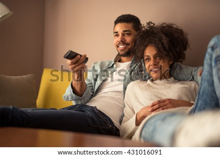 Cropped shot of a young african american couple watching television at home Royalty-Free Stock Photo #431016091