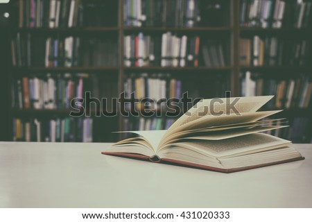 Close up of open book on desk and bookshelf with vintage filter blur background #431020333