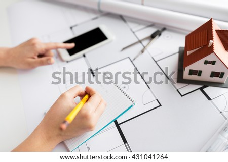 business, architecture, building, construction and people concept - close up of architect hand with living house blueprint and smarphone writing to notebook #431041264
