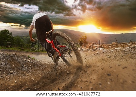 Man on mountain bike rides on the trail on a stormy sunset. Royalty-Free Stock Photo #431067772