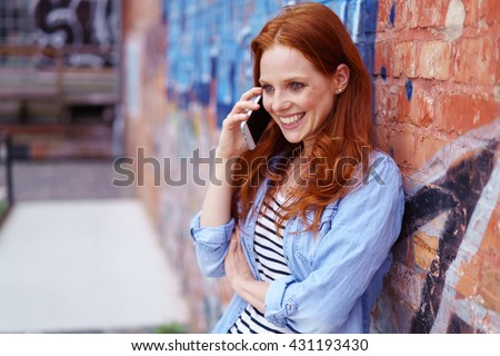 Pretty young redhead woman chatting on her mobile phone in town leaning against a graffiti covered brick wall smiling as she listens to the conversation #431193430