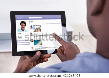 Close-up Of A Person Using Social Networking Site On Digital Tablet #431265403