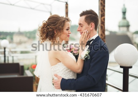 Happy wedding couple, bride, groom kissing with view of old city #431670607