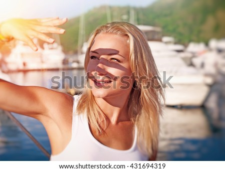 Portrait of a beautiful blond girl covering face by hand of bright sun light, spending weekend on the yacht, happy summer vacation #431694319