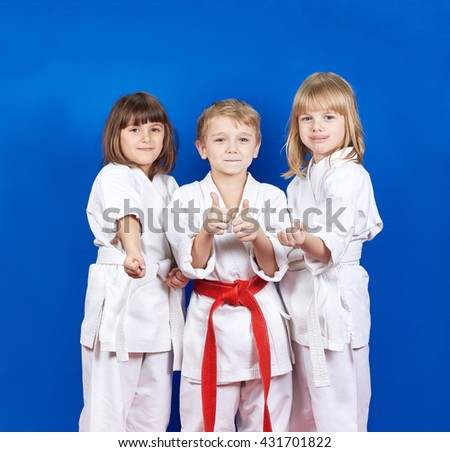 Three cheerful child standing in a white kimono on a blue background #431701822