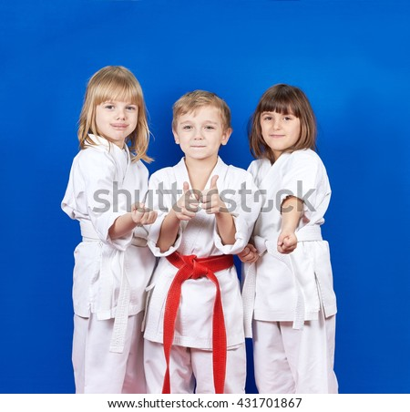 Three cheerful child standing in a white kimono on a blue background #431701867